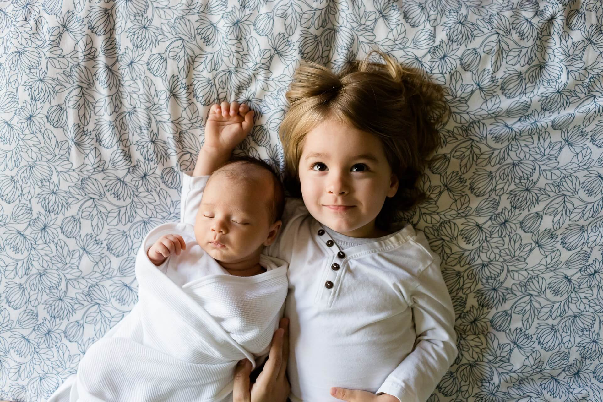 Siblings dressed in white lying on bed